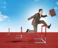 Businessman hopping over treadmill barrier Stock Photo