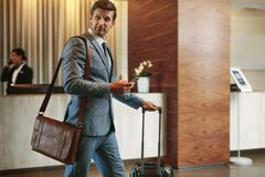 Businessman in hotel hallway with phone and baggage. Businessman walking in hotel hallway with mobile phone and baggage. Male business traveler arriving at his Royalty Free Stock Photography