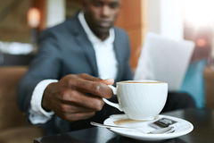 Businessman at hotel lobby drinking coffee Stock Image