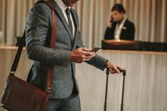 Businessman in hotel lobby with phone and luggage. Cropped shot of businessman in hotel lobby with mobile phone and luggage. Male business traveler arriving at royalty free stock photos