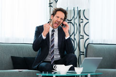 Businessman in hotel is on the phone Royalty Free Stock Photo