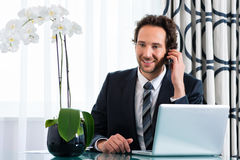 Businessman in hotel is on the phone Royalty Free Stock Photography