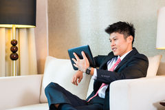 Businessman in hotel room working with tablet Stock Photos