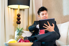 Businessman in hotel room working with tablet Stock Photo