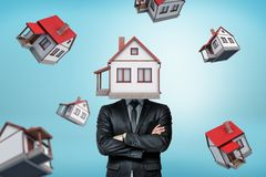 A businessman with a house instead of his head stands with folded arms on a background with many other houses. royalty free stock images