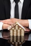 Businessman with house made of currency at desk Stock Images