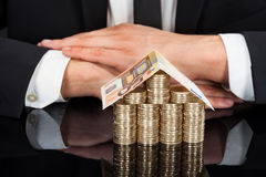 Businessman With House Made Of Currency At Desk Royalty Free Stock Photography