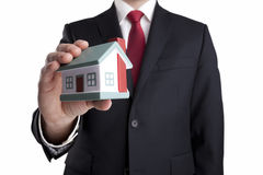Businessman with house miniature in hand Stock Photos