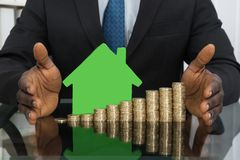 Businessman With House Model And Coins Stock Image