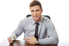 Businessman with house model by a desk. Royalty Free Stock Photography