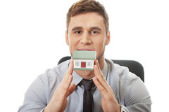 Businessman with house model by a desk. Stock Photos