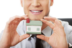 Businessman with house model by a desk. Stock Image