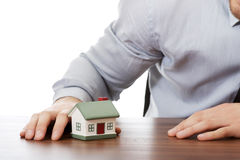 Businessman with house model by a desk. Stock Photo