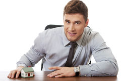 Businessman with house model by a desk. Royalty Free Stock Photo
