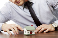 Businessman with house model by a desk. Stock Images