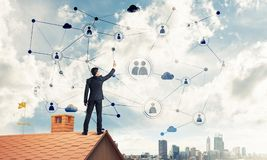 Businessman on house roof presenting networking and connection c Royalty Free Stock Images