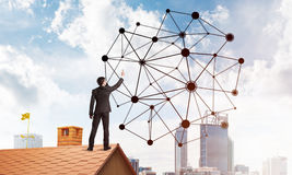 Businessman on house roof presenting networking and connection concept. Mixed media Stock Images