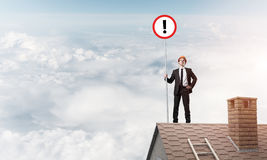 Businessman on house top showing sign with exclamation mark. Mix. Young businessman with roadsign in hand standing on brick roof. Mixed media Royalty Free Stock Image