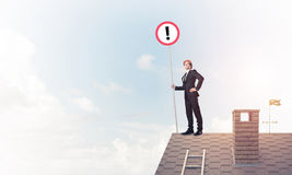 Businessman on house top showing sign with exclamation mark. Mix. Young businessman with roadsign in hand standing on brick roof. Mixed media Stock Photos