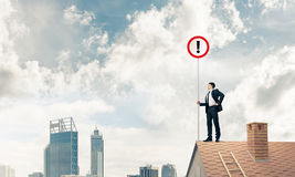 Businessman on house top showing sign with exclamation mark. Mix. Young businessman with roadsign in hand standing on brick roof. Mixed media Royalty Free Stock Images