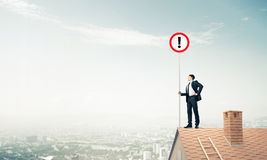 Businessman on house top showing sign with exclamation mark. Mix. Young businessman with roadsign in hand standing on brick roof. Mixed media Royalty Free Stock Photography