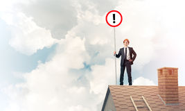 Businessman on house top showing sign with exclamation mark. Mix. Young businessman with roadsign in hand standing on brick roof. Mixed media Stock Image