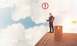 Businessman on house top showing sign with exclamation mark. Mix. Young businessman with roadsign in hand standing on brick roof. Mixed media Royalty Free Stock Photos