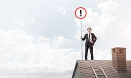 Businessman on house top showing sign with exclamation mark. Mix. Young businessman with roadsign in hand standing on brick roof. Mixed media Stock Images