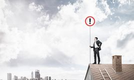Businessman on house top showing sign with exclamation mark. Mix. Young businessman with roadsign in hand standing on brick roof. Mixed media Stock Photography