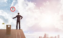 Businessman on house top showing sign with exclamation mark. Mixed media. Young businessman with roadsign in hand standing on brick roof. Mixed media Stock Photography