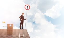 Businessman on house top showing sign with exclamation mark. Mixed media. Young businessman with roadsign in hand standing on brick roof. Mixed media Royalty Free Stock Photos