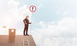 Businessman on house top showing sign with exclamation mark. Mixed media. Young businessman with roadsign in hand standing on brick roof. Mixed media Stock Images