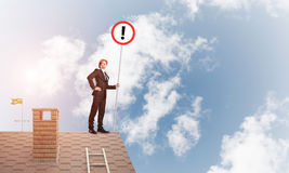 Businessman on house top showing sign with exclamation mark. Mixed media. Young businessman with roadsign in hand standing on brick roof. Mixed media Royalty Free Stock Image