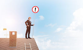 Businessman on house top showing sign with exclamation mark. Mixed media. Young businessman with roadsign in hand standing on brick roof. Mixed media Royalty Free Stock Images
