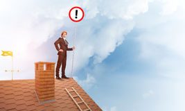 Businessman on house top showing sign with exclamation mark. Mixed media. Young businessman with roadsign in hand standing on brick roof. Mixed media Royalty Free Stock Photography