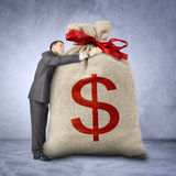 Businessman hugging bag with dollar sign Royalty Free Stock Photography