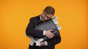 Businessman hugging briefcase full of money, isolated on yellow background