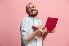 Businessman hugging laptop. Love to computer concept. Attractive male half-length front portrait, trendy pink studio backgroud. Young emotional bearded man Stock Photos