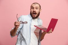Businessman hugging laptop. Love to computer concept. Attractive male half-length front portrait, trendy pink studio backgroud. Young emotional bearded man Stock Photo