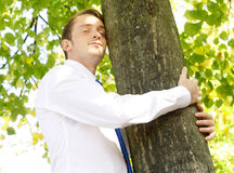 Businessman hugging tree Royalty Free Stock Image