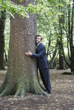 Businessman Hugging Tree Trunk In Forest Stock Photo