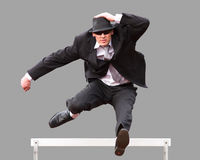 Businessman in hurdling. A business man is jumping over a hurdle in track and field Stock Photo