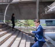 Businessman in a hurry checking time and running, he is late for work his business appointment. Stock Photo