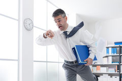 Businessman in a hurry checking time Stock Images