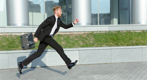 Businessman in hurry. Handsome modern hipster businessman with bag hurrying to work. Red-haired man in black business suit does not want to miss meeting Royalty Free Stock Photography