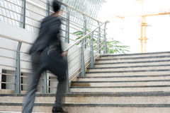 Businessman in hurry. Motion blurred people over office building Stock Photography