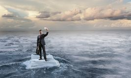 Surfing sea on ice floe. Mixed media. Businessman on ice block floating in sea and making selfie. Mixed media . Mixed media Royalty Free Stock Images