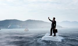 Surfing sea on ice floe. Mixed media. Businessman on ice block floating in sea and making selfie. Mixed media Royalty Free Stock Photo