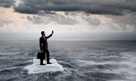 Surfing sea on ice floe. Mixed media. Businessman on ice block floating in sea and making selfie. Mixed media Royalty Free Stock Photography