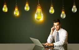Businessman with idea bulbs. Businessman sitting at the black table with idea bulbs on the background Stock Photography